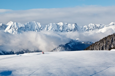 Panoramic View on Mountains and Two People Trekking in French Alps in Winter photo