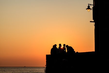 Group of People Watching Sunset in Riomaggiore, Italy photo