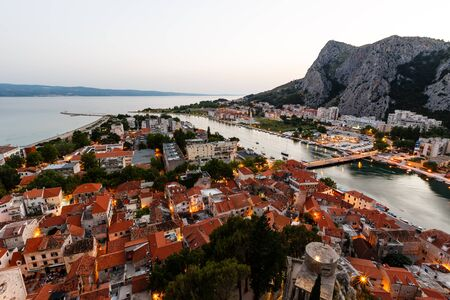 Arial View on Illuminated Town of Omis and River Cetina Gorge in the Evening, Croatia photo
