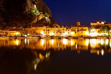 bandera de croacia: Iluminada Castillo Pirata y Ciudad de Omis reflejo en el río Cetina en la noche, Croacia