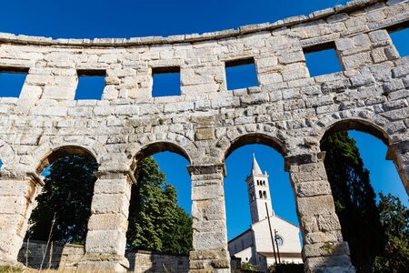 White Church Framed in the Arch of Ancient Roman Amphitheater in Pula, Istria, Croatia photo