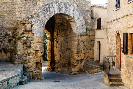 escultura romana: Calle estrecha y la puerta etrusca de Volterra en Italia