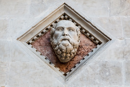 heads old building facade: Head Carved in Marble on the Facade of the Baptistery of Siena Cathedral, Italy