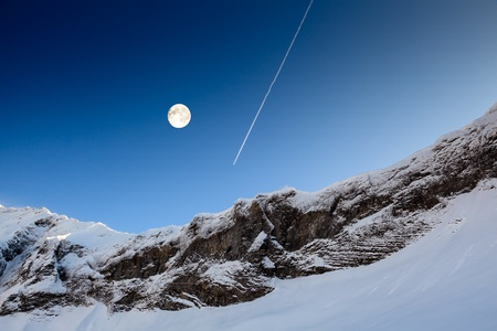 Full Moon and Airplane Trail in Blue Sky above Mountain Peak, French Alps, Megeve photo