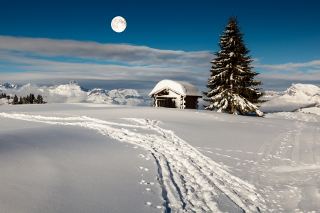 fool moon: Full Moon above Small Hut and Fir Tree on the Top of the Mountain in Megeve, French Alps