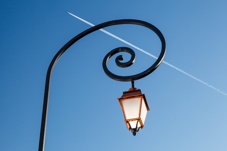 street lamps: Shining Backlit Streetlamp and Airplane Trail in Background, Megeve, France