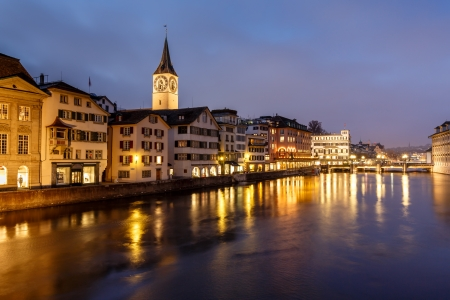 Illuminated Saint Peter Church and Houses along Limmat River Bank in the Evening, Zurich, Switzerland