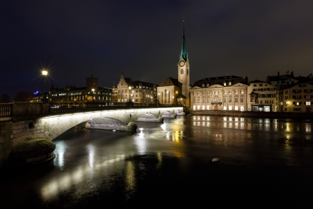 Illuminated Fraumunster Church and River Limmat in Zurich, Switzerland photo