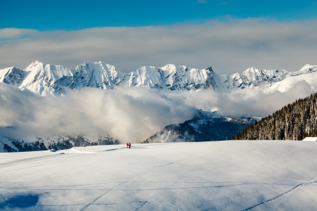 Panoramic View on Mountains and Two People Walking in French Alps in Winter photo