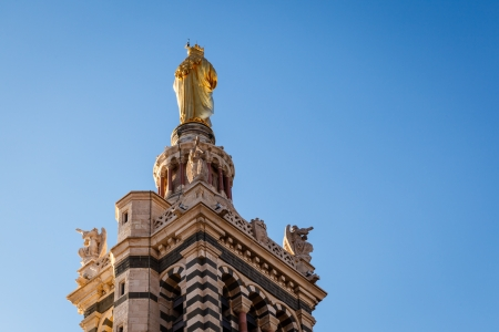Golden Statue of the Madonna Holding the little Jesus on the top of Notre-Dame de la Garde in Marseilles, France photo