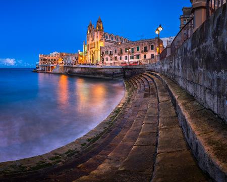 julian: Balluta Bay and Church of Our Lady of Mount Carmel in Saint Julien, Malta Stock Photo