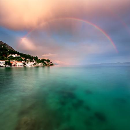 beach rain: Rainbow over Rocky Beach and Small Village after the Rain Dalmatia Croatia