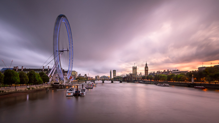 LONDON, UNITED KINGDOM - OCTOBER 6, 2014: London Eye and Westminster Palace in London. The largest Ferris Wheel in Europe, structure of the London Eye is 135 meters tall and 120 meters in diameter.