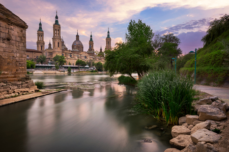 Basilica de Nuestra Senora del Pilar and Ebor River in the Evening, Zaragoza, Aragon, Spain Фото со стока