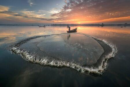Taung Tha Man Lake, Myanmar - November 12, 2018: Fisherman Throwing Traditional Net Early in the Morning
