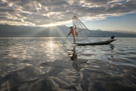 nle Lake, Myanmar - November 14, 2018: Burmese Fisherman on the Boat with Traditional Conical Net in the Morning, Lake Inle, Myanmar