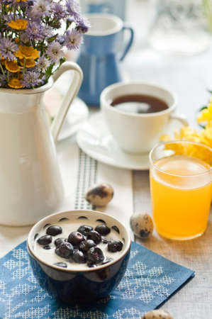 Breakfast spread with blueberries, orange juice and coffee set with beautiful blue and yellow flowers  photo