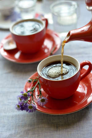 coffee maker: Pouring Coffee from a red teapot in a red cup