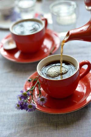 tomando refresco: Servir el café de un vaso de agua de color rojo en una taza de color rojo