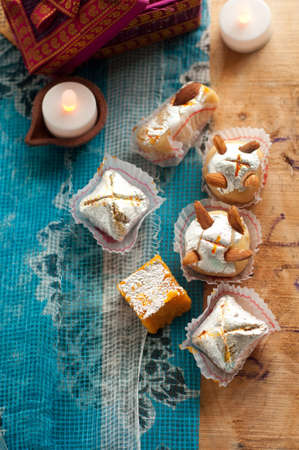 diyas: Diwali Sweets set in a Rustic India setting with rustic lamps and traditional Indian printed blue cloth