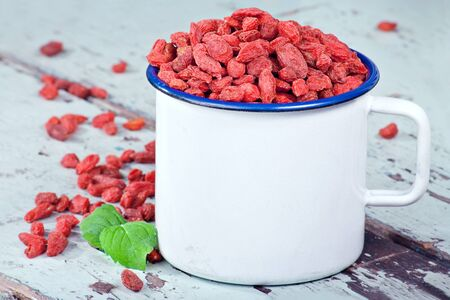 Red goji berries on a light blue rustic wooden background photo