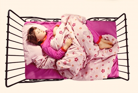 sleeping kid: Young girl sleeping in a pink-colored bed, angly from above Stock Photo