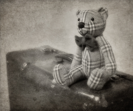Vintage-style teddy bear and old suitcase with textured blackground photo