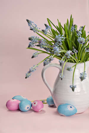 Blue hyacinths in a white vase with colored eggs and a pink background photo