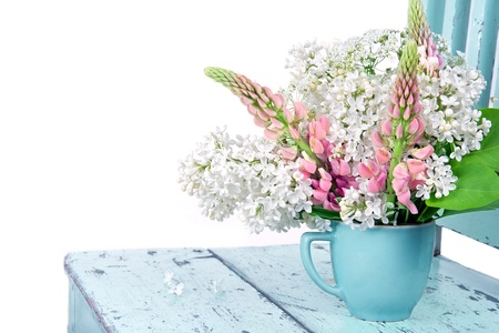 Arrangement of wildflowers on a rustic light blue chair isolated on white photo