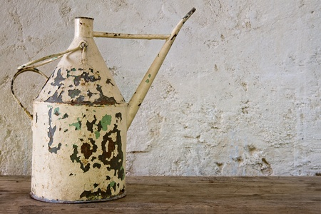 patina: Antique rustic watering can on a wooden table