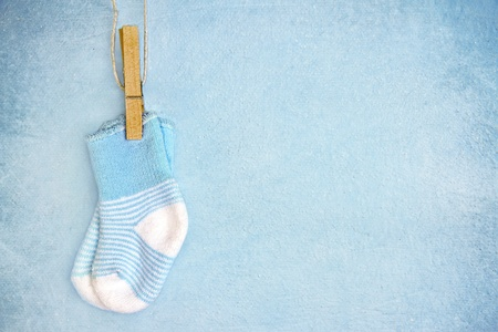 parents with baby: Blue baby socks on a textured rustic background with copy space