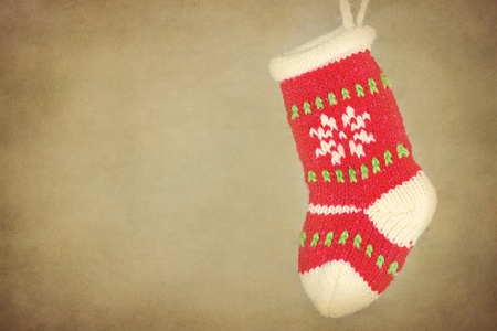 Cute knitted Christmas sock  stocking hanging on rustic vintage textured background