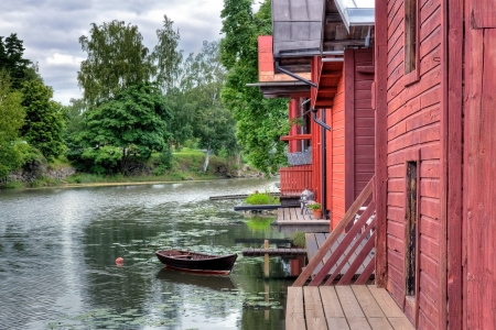 finnish: Red wooden buildings and a rowing boat by a river in Porvoo Finland