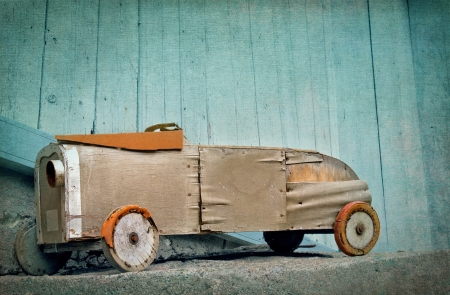 antique car: Old wooden rustic toy car on a light blue textured artistic background