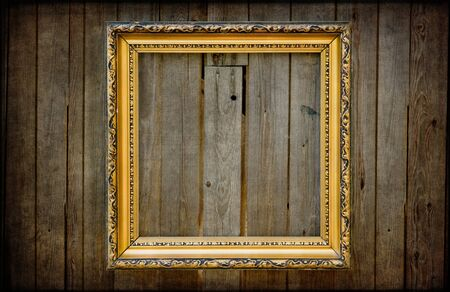 Golden empty frame on a wooden rustic wall with vintage textured editing photo
