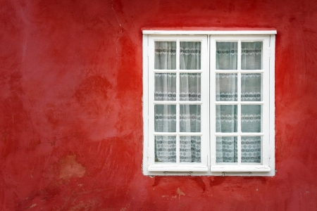 Decorative white window on an old red stucco wall photo