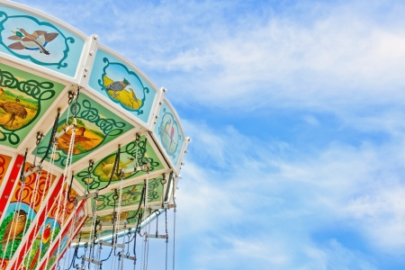 themes: Closeup of a colorful carousel with blue sky background and copy space