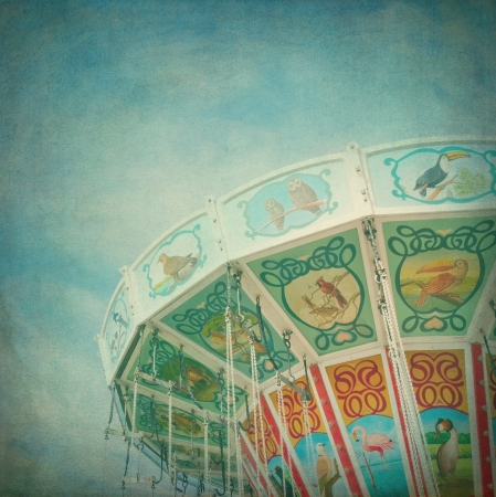 amusement park ride: Closeup of a colorful carousel with blue sky background, with vintage style texture editing Stock Photo