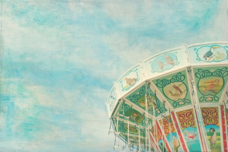 Closeup of a colorful carousel with blue sky background, with painterly textured editing photo