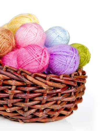 basket embroidery: Colorful woolen yarn in a wicker basket isolated on white
