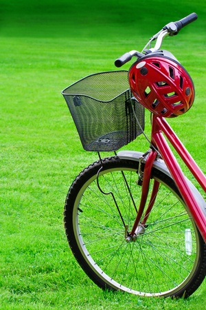 Close-up of women�s red mountain bike and a helmet in green grass summer background photo