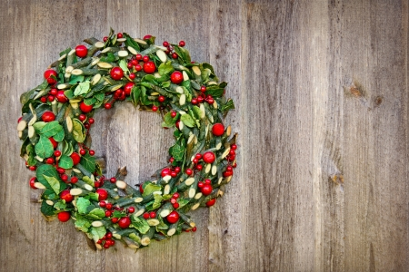 Rustic Christmas wreath hanging on a wooden vintage background with copy space photo