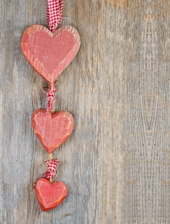 Decorative red wooden Christmas hearts on rustic background with copy space