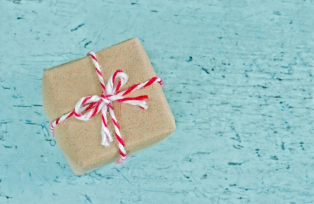 Gift Box Wrapped In Brown Paper With Red Striped String On Light Blue Shabby Chic Background