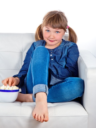 Pretty little girl sitting on a sofa eating popcorn photo