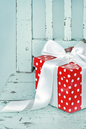 Red gift box with white bow on a light blue background photo
