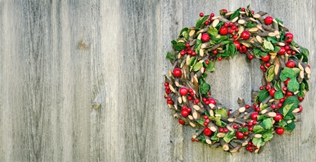Rustic Christmas wreath hanging on a wooden vintage background with copy space  Banco de Imagens
