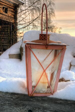 old barn in winter: Rustic lantern in snowy winter evening in front of an old wooden barn