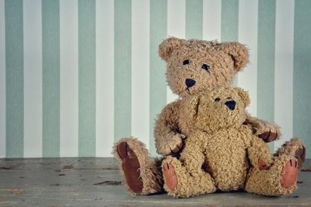 osos de peluche: Ajuste de la vendimia de dos osos de peluche que abraza, fondo verde con rayas Foto de archivo