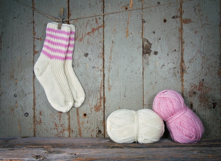 White and pink woolen socks in vintage setting - knitting concept with copy space photo